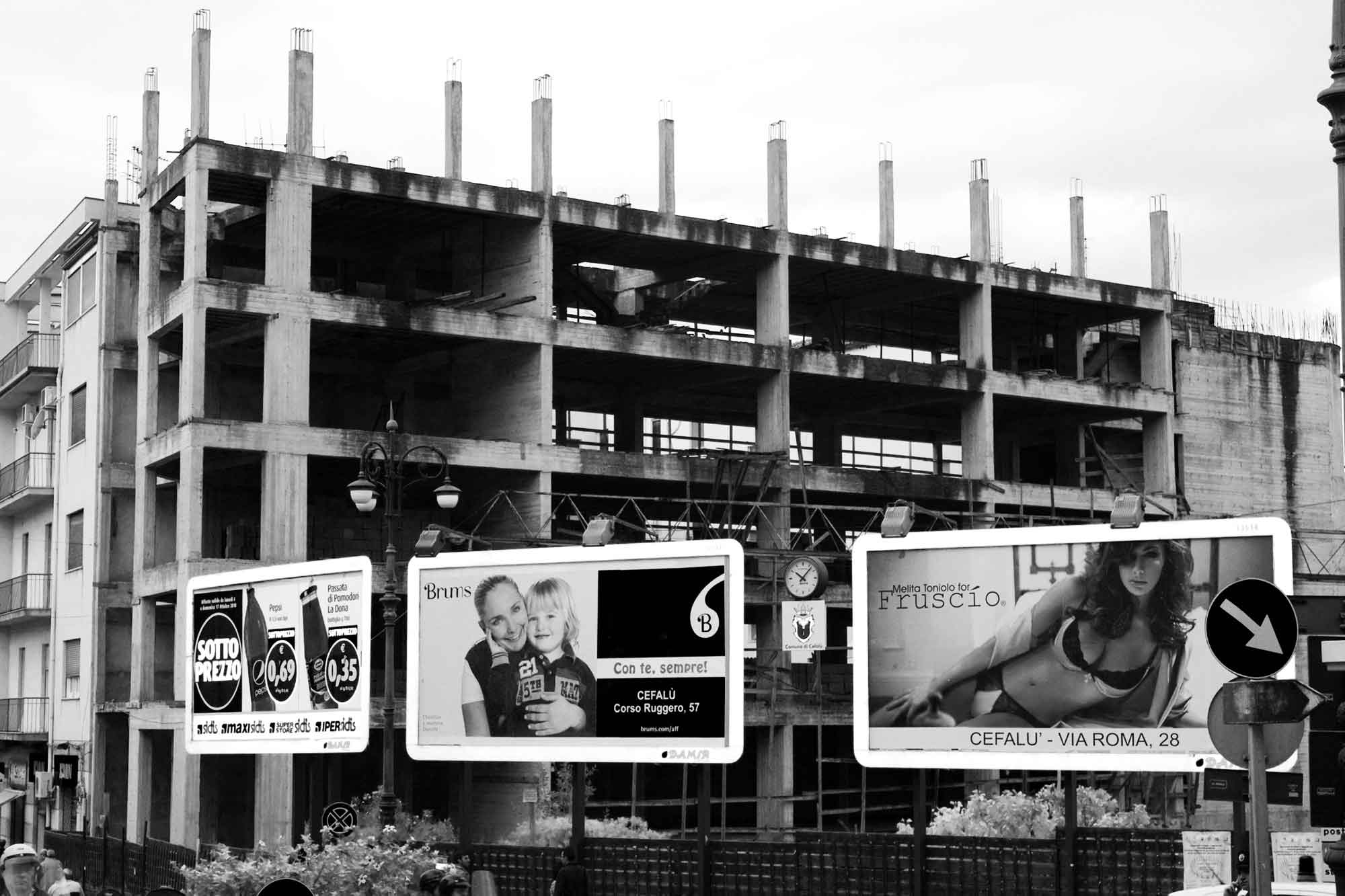 Bauskelett mit Werbetafeln im Vordergrund, Cefalù, Sizilien