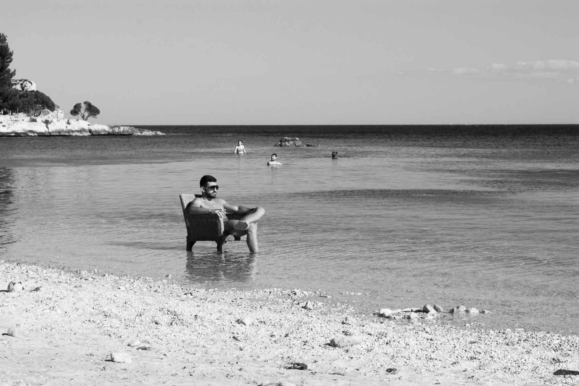 Italiener mit Sonnenbrille im Wasser am Strand von Sardinien